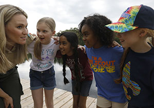 Cub girls and leader on pier
