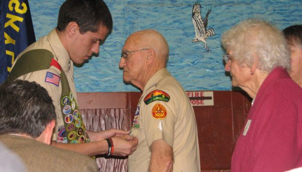 George Maher receiving Eagle Scout award from grandson as wife, Marilyn, looks on