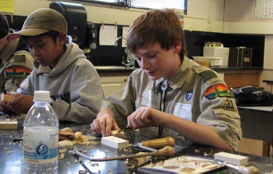 Scouts learning woodworking at Merit Badge Midway