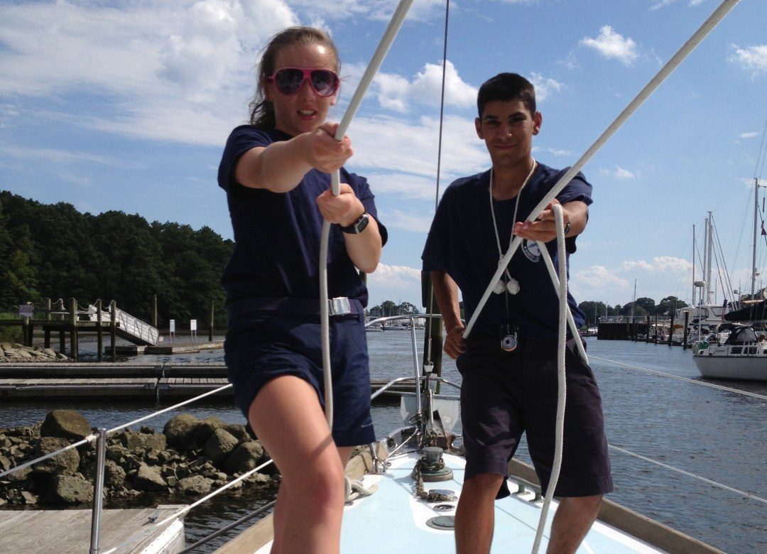 Sea Scout girl and boy on vessel pulling handling ropes