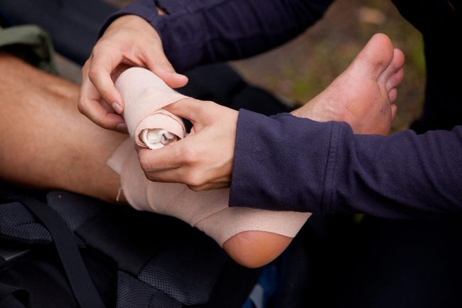 First aid, leg tensor bandage being applied outdoors