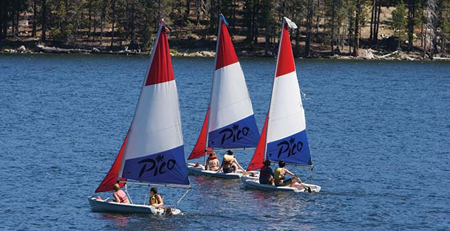 Scouts sailing three boats on Huntington Lake
